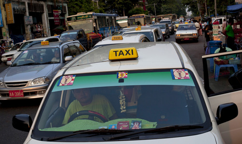 ADVANCE FOR USE MONDAY, APRIL 29, 2013 AND THEREAFTER - A taxi with 969 logos on the windshield stops for a passenger in Yangon, Myanmar on March 31, 2013. (AP Photo/Gemunu Amarasinghe)
